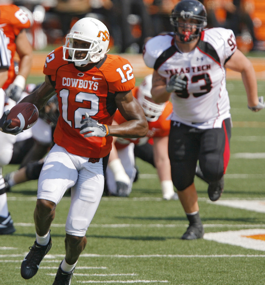 Oklahoma State's Adarius Bowman (12) races up field past the Texas Tech defense during the first half of the college football game between the Oklahoma State University Cowboys (OSU) and the Texas Tech University Red Raiders (TTU) at Boone Pickens Stadium  on Saturday, Sept. 22, 2007, in Stillwater, Okla. 