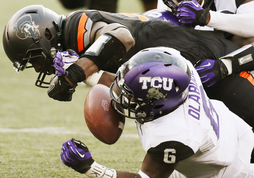 Photo - Oklahoma State's Blake Jackson (18) fumbles the ball as TCU's Elisha Olabode (6) defends in the fourth quarter during a college football game between Oklahoma State University (OSU) and Texas Christian University (TCU) at Boone Pickens Stadium in Stillwater, Okla., Saturday, Oct. 27, 2012. OSU recovered the fumble. Photo by Nate Billings, The Oklahoman