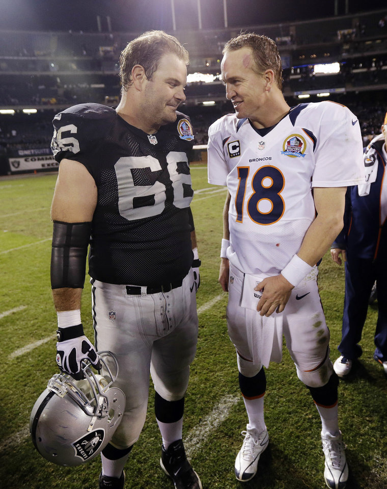 Photo - Denver Broncos quarterback Peyton Manning, right, is greeted by Oakland Raiders guard Cooper Carlisle, left, at the end of their NFL football game in Oakland, Thursday, Dec. 6, 2012. Denver won 26-13. (AP Photo/Marcio Jose Sanchez)