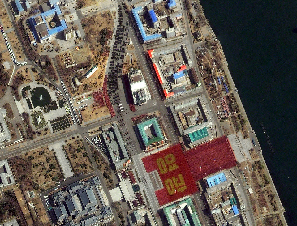 Photo -   FILE - This April 15, 2012 satellite image provided by DigitalGlobe shows a parade held to mark the 100th anniversary of Kim Il-sung's birthday Pyongyang, North Korea. The parade can be seen from the top center of the frame as it makes it way toward Kim Il Sung Square in the lower right hand corner where a large formation of people in red and gold clothing spell out in Korean the characters for the word