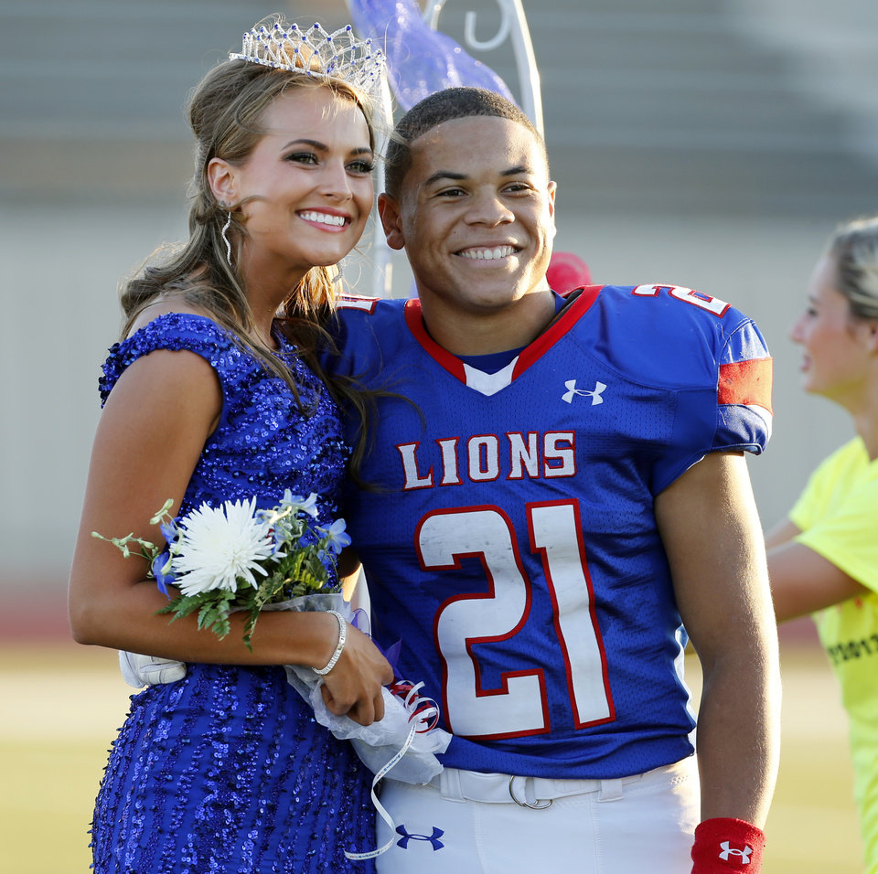 Moore's Mariah Davis is crowned homecoming queen and is escorted by Ryan Lujan-Leonard as the Moore High School Lions play the Putnam City North Panthers in high school football on Thursday, Oct. 3, 2013, in Moore, Okla.  Photo by Steve Sisney, The Oklahoman