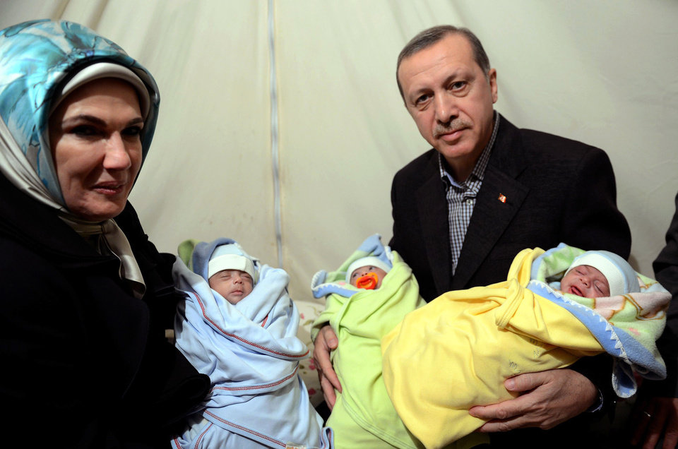 Photo - In this photo provided by Turkish Prime Minister's Press Service, Turkish Prime Minister Recep Tayyip Erdogan, and his wife Emine Erdogan hold newly born babies during a visit to a Syrian refugee camp in Sanliurfa, Turkey, Sunday, Dec. 30, 2012. Erdogan repeated a call on Syrian President Bashar Assad to step down. (AP Photo/Kayhan Ozer)