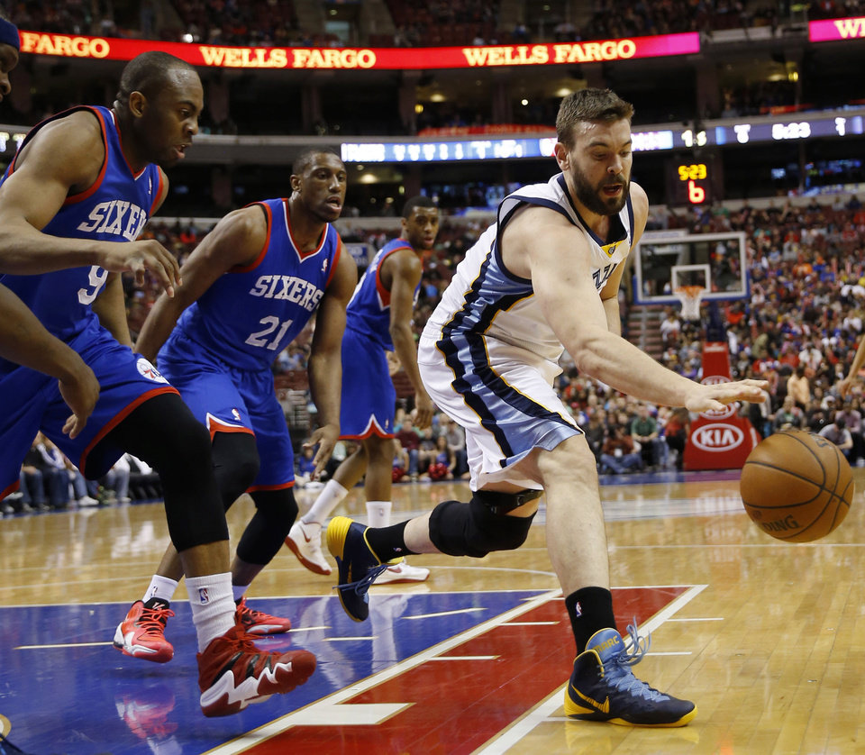 Photo - Memphis Grizzlies' Marc Gasol, right, of Spain, chases down a loose ball as Philadelphia 76ers' James Anderson, left, and Thaddeus Young look on during the first half of an NBA basketball game, Saturday, March 15, 2014, in Philadelphia. (AP Photo/Matt Slocum)