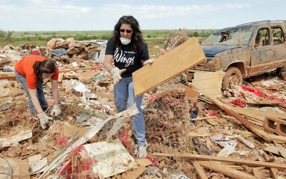 Photo - Volunteers Susan Turner, right, and daughter Lauren Turner search through debris at the Hide-A-Way Mobile Home Park in Woodward, Okla., Monday, April 16, 2012.  A tornado struck the town early Sunday morning. Photo by Nate Billings, The Oklahoman