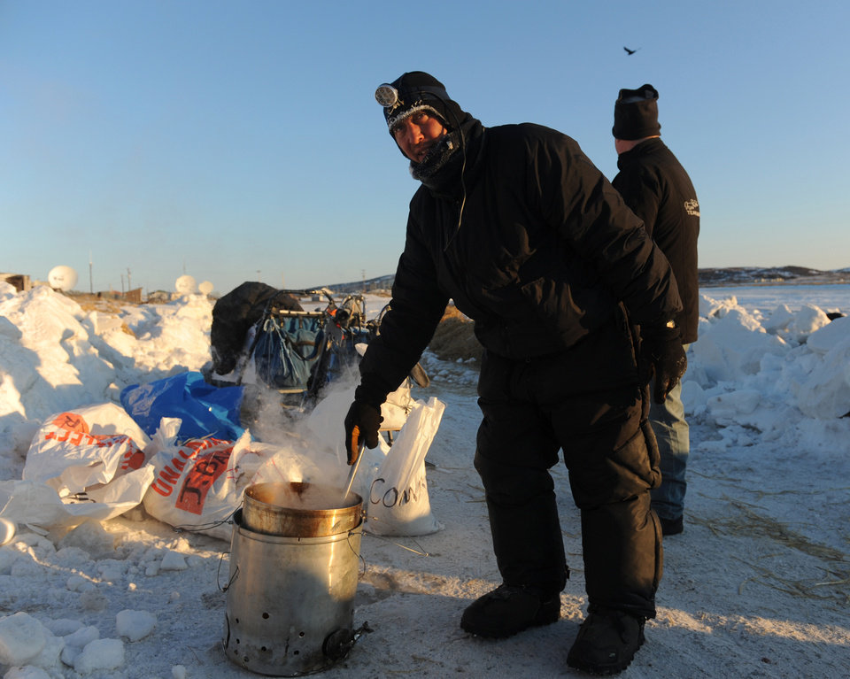 Photo - Iditarod musher John Baker, from Kotzebue, Ak, prepares dog food for his team at the Unalakleet checkpoint at sunrise during the 2014 Iditarod Trail Sled Dog Race on Sunday, March 9, 2014. (AP Photo/The Anchorage Daily News, Bob Hallinen)