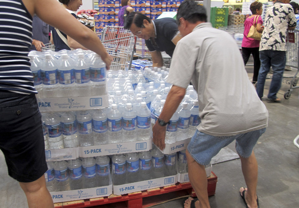 Photo - Shoppers lift cases of bottled water in preparation for a hurricane and tropical storm heading toward Hawaii at the Iwilei Costco in Honolulu on Tuesday, Aug. 5, 2014. Two big storms so close together is rare in the eastern Pacific. Hurricane Iselle could make landfall by Friday and Tropical Storm Julio could hit two or three days later, weather officials said. (AP Photo/Audrey McAvoy)