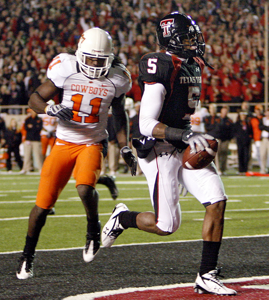 Photo - Texas Tech's Michael Crabtree (5) scores a touchdown in front of Oklahoma State's T.J. Bell (11) during the second half of the college football game between the Oklahoma State University Cowboys (OSU) and the Texas Tech Red Raiders at Jones AT&T Stadium on Saturday, Nov. 8, 2008, in Lubbock, Tex.BY CHRIS LANDSBERGER/THE OKLAHOMAN