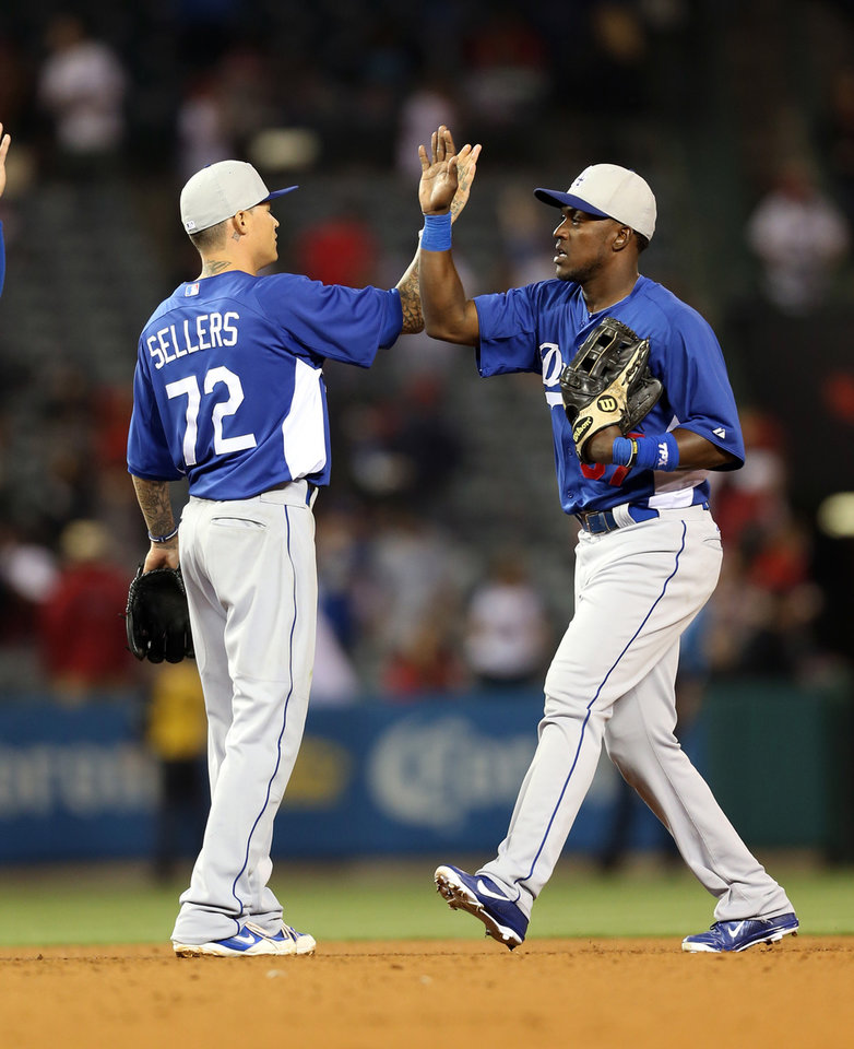 Los Angeles Dodgers Justin Sellers (72), left and Elian Herrera celebrate a 3-0 win over the Los Angeles Angels in Anaheim, Calif., on Thursday, March 28, 2013. (AP Photo/Christine Cotter)