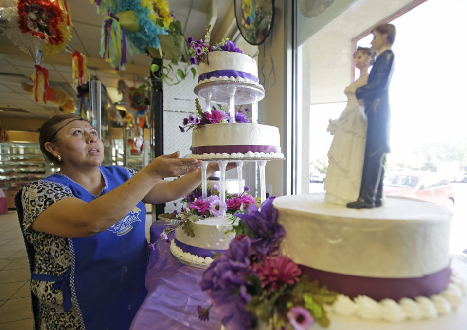 Photo - In this July 31, 2014, photo, Basilia Buendia of Panaderia Flores, adjusts a three-tier wedding cake on Salt Lake City's west side. Panaderia Flores offers sweet breads, pineapple or pumpkin empanadas and tamales. (AP Photo/Rick Bowmer)