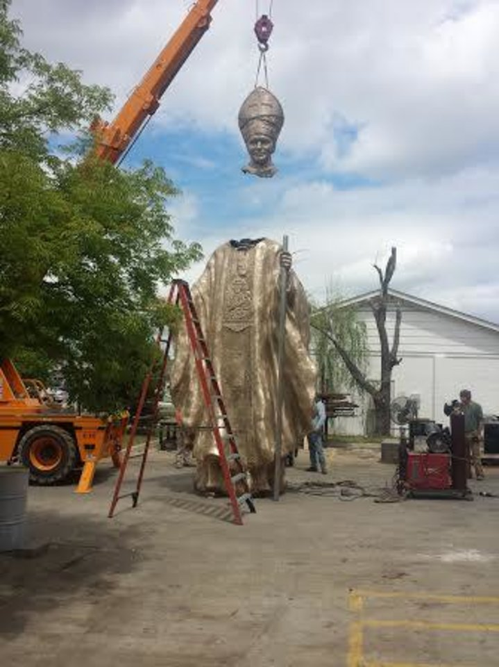 Photo -  A crane is used to mount the head of Pope John Paul II onto its bronze body outside The Crucible in Norman. [PHOTOs PROVIDED]