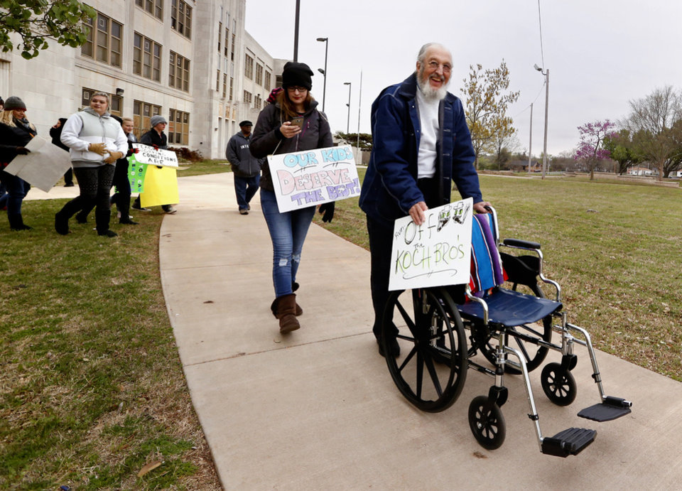 Photo -  Former teachers union president Ted Metscher uses a wheelchair as a walker as he and others begin a march from Northeast Academy to the state Capitol to protest education funding. [Photo by Steve Sisney, The Oklahoman]   STEVE SISNEY