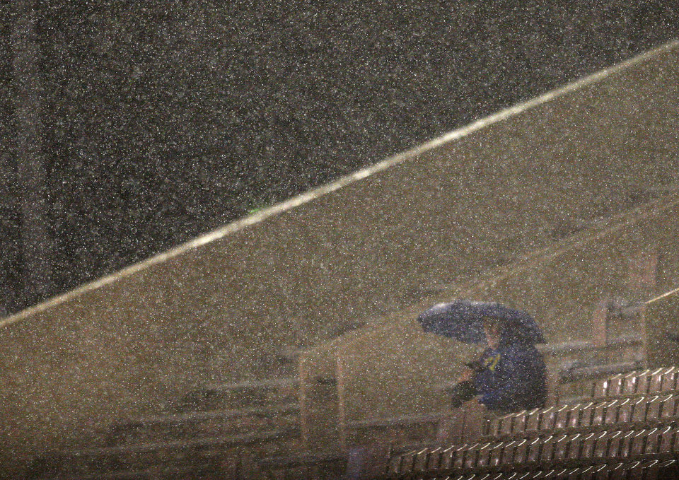 Photo - A fan waits out a rain delay before a college football game between the Oklahoma State University Cowboys (OSU) and the University of Tulsa Golden Hurricane (TU) at H.A. Chapman Stadium in Tulsa, Okla., Saturday, Sept. 17, 2011. Photo by Sarah Phipps, The Oklahoman  ORG XMIT: KOD