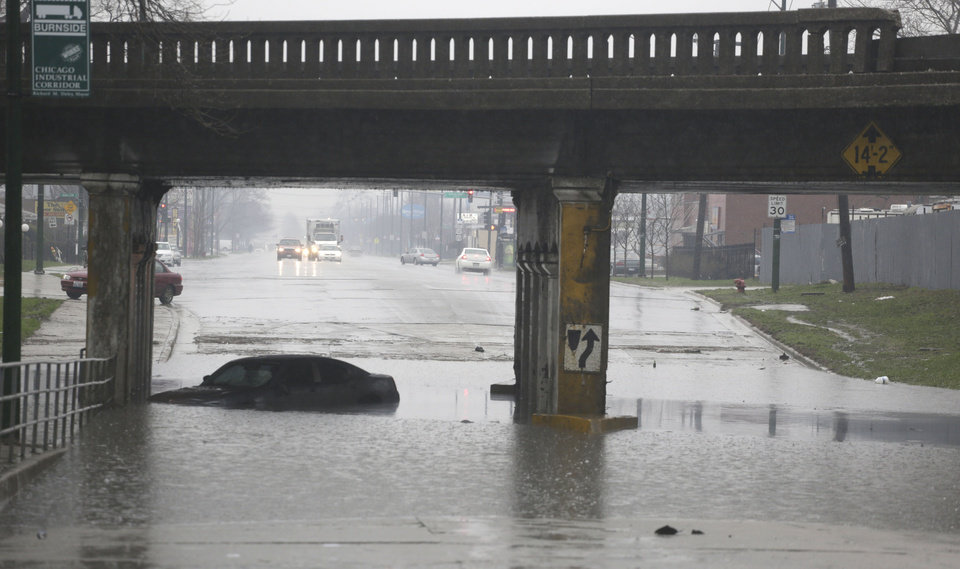 Photo - An abandoned car bobs in standing water under an overpass Thursday, April 18, 2013, in Chicago.  Blasts of torrential rain and widespread flooding forced authorities to shut segments of major expressways, and hundreds of flights were scrapped. (AP Photo/M. Spencer Green)
