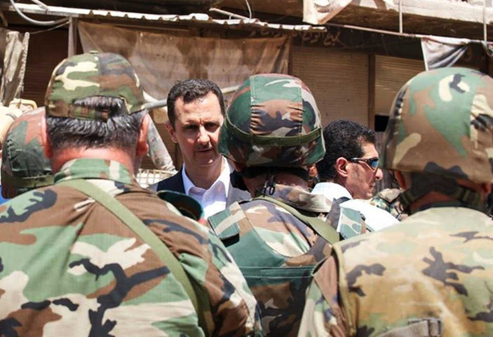 Photo - FILE - This Aug. 1, 2013 file photo posted on the official Facebook page of the Syrian Presidency shows Syrian President Bashar Assad talking with soldiers during Syrian Arab Army Day in Darya, Syria. For the first time in the Syrian civil war, militants linked to al-Qaida are hunkered down on Israel's doorstep. Israelis in the lush, hilly Golan Heights who have long considered Assad their bitter foe are now worried about something more ominous, that they could become the rebels' next target.  The arrival of the Nusra Front, al-Quaida's Syrian branch, comes just two weeks after Israel ended a 5-day war against Hamas on its southern border, giving the conflict weary nation another reason to worry. (AP Photo/Syrian Presidency via Facebook, File)