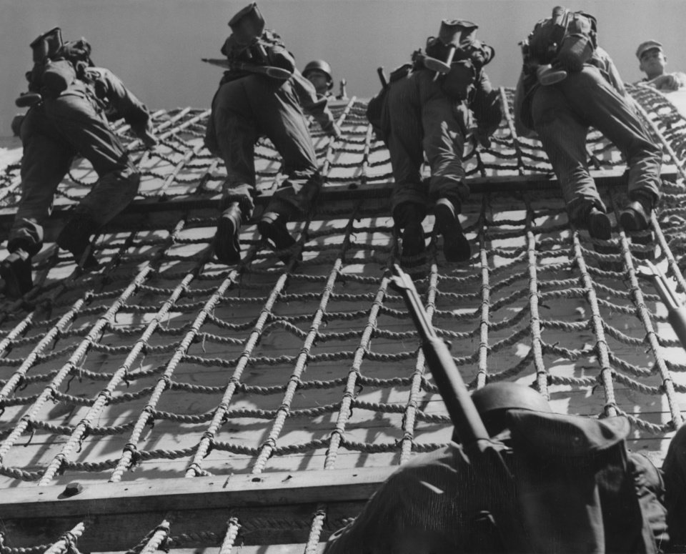 """Photo - Thunderbirds Undergo Amphibious Training in Japan.  The 45th division is undergoing amphibious training on Hokkaido, Japan, but no one is getting wet.  The former Oklahoma national guardsmen are running through practice landings using wooden 'mock ups' for troop transports and landing boats.  The 45th men are taking the training under supervision of the marine corps and navy.   By Wayne Mackey Does Red China know more about the disposition of troops in Oklahoma's 45th infantry division than the American public itself?  That's a question hundreds of Oklahoma families are asking each other this week following Radio Peping's charge that California's 40th and Oklahoma's 45th will be used in a United Nations plan to 'pocket the whole of North Korea.'  Both former national guard outfits presently are training in Japan--the 40th on Honshu, Japan's main island, and the 45th on Hokkaido, northernmost Japanese home island.""""  Photo by Jack Gunter of 45th Division News Photo.  Original date unknown.  Published in The Oklahoma City Times 10/05/1951."""