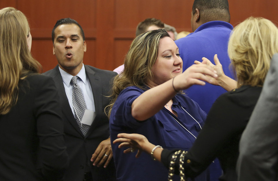 Photo - George Zimmerman's family and friends celebrate after Zimmerman's not guilty verdict was read in Seminole Circuit Court in Sanford, Fla. on Saturday, July 13, 2013. Jurors found Zimmerman not guilty of second-degree murder in the fatal shooting of 17-year-old Trayvon Martin in Sanford, Fla. (AP Photo/Gary W. Green, Pool) ORG XMIT: FLJR408