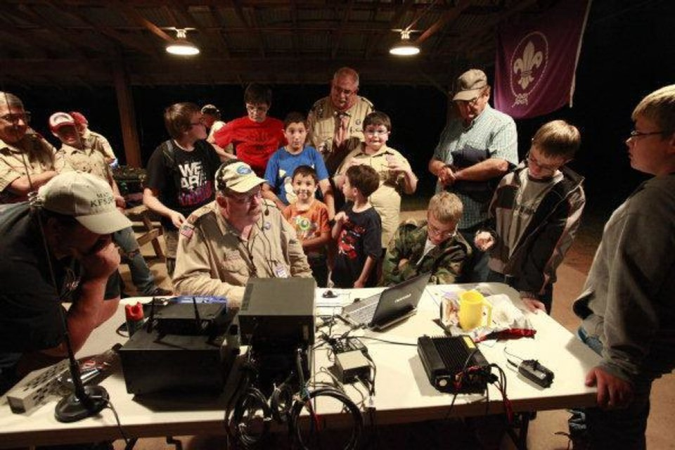 Photo - Mark Hamblin, center, makes contact with a radio operator in Australia during the 54th Jamboree-On-The -Air last weekend.  David McDaniel - THE OKLAHOMAN