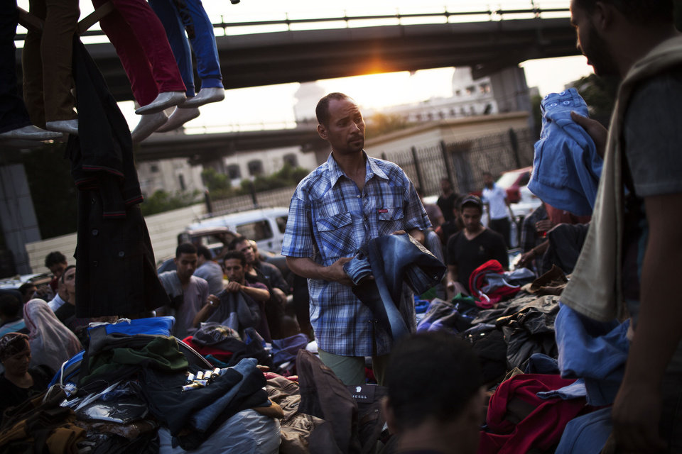 Photo - An Egyptian street vendor works at his stall in the Ataba market on the eve of Eid al-Adha, or Festival of the Sacrifice, one of the most important celebrations in the Muslim calendar, in Cairo, Egypt, Monday, Oct. 14, 2013. (AP Photo/Manu Brabo)