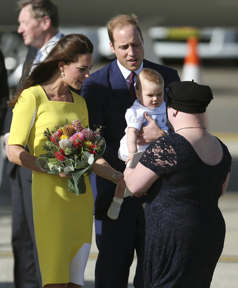Photo - Britain's Prince William back right, and his wife Kate, the Duchess of Cambridge, along with their son Prince George are presented with flowers by Joscelyn Sweeney  upon arriving in Sydney, Australia, Wednesday, April 16, 2014. The Duke and Duchess of Cambridge are on a three-week tour of Australia and New Zealand, the first official trip overseas with their son, Prince George. (AP Photo/Rob Griffith)