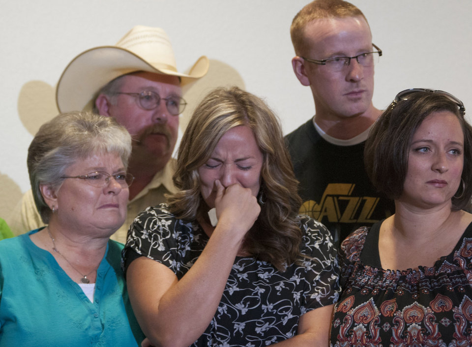 Christy Ivie, center, wife of Nicolas Ivie, holds back tears as she is surrounded by her family, her father Tracy and mother DeAnn Morris, left, and her sister, Jan Cloward, right front, and brother, Travis Morris, right back, during news conference about slain U.S. Customs and Border Protection agent Nicolas Ivie, on Thursday, Oct. 4 , 2012, at the Cochise College in Sierra Vista, Ariz. Ivie was gunned down Tuesday, Oct 2, as he responded to a tripped sensor on the USA side of the border fence, near the small border town of Naco, Ariz. Ivie's partner was also hit in gunfire during the exchange, but was released from a Tucson hospital on Wednesday. (AP Photo/Gary M. Williams)