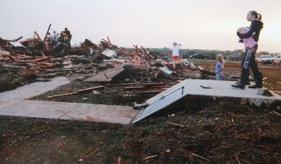 Photo - Copy photo of Chad and Becky Brown's home destroyed in the May 24, 2011 tornado, Wednesday, May 16, 2012. The children are standing on the storm shelter were they road out the tornado.   Photo provided. Copied By David McDaniel/The Oklahoman