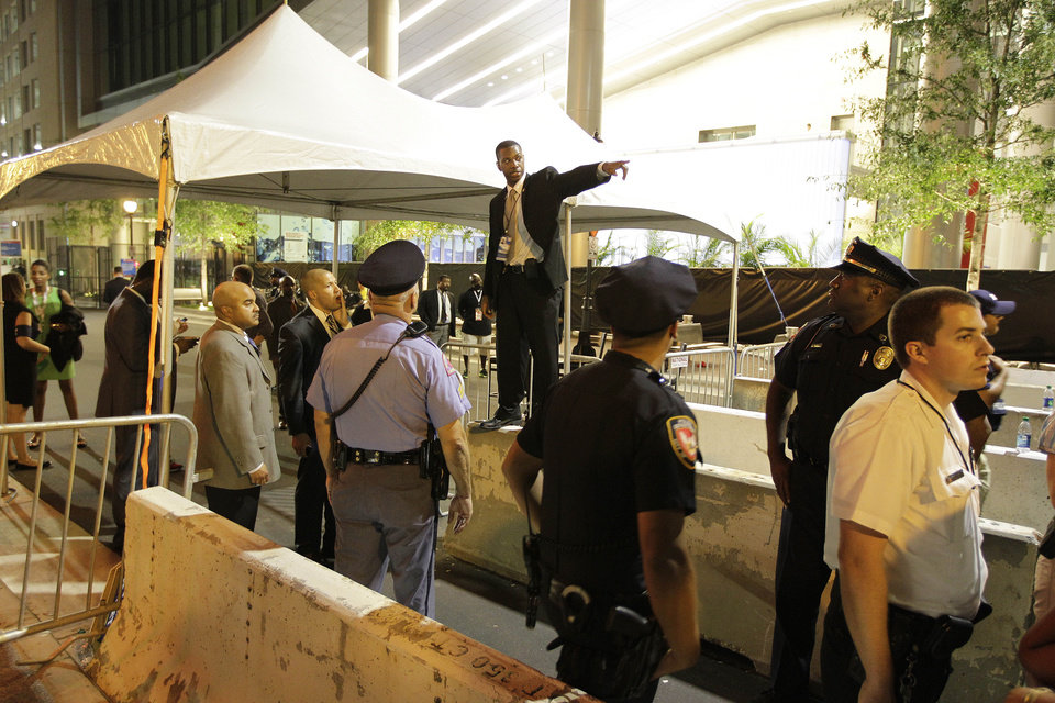 Photo - A security official speaks to convention goers as they were asked to move outside a security zone, Wednesday, Sept. 5, 2012, in Charlotte, N.C., during the second day of the Democratic National Convention.The entrance was delayed because of safety concerns. (AP Photo/Chuck Burton) ORG XMIT: XDNC123