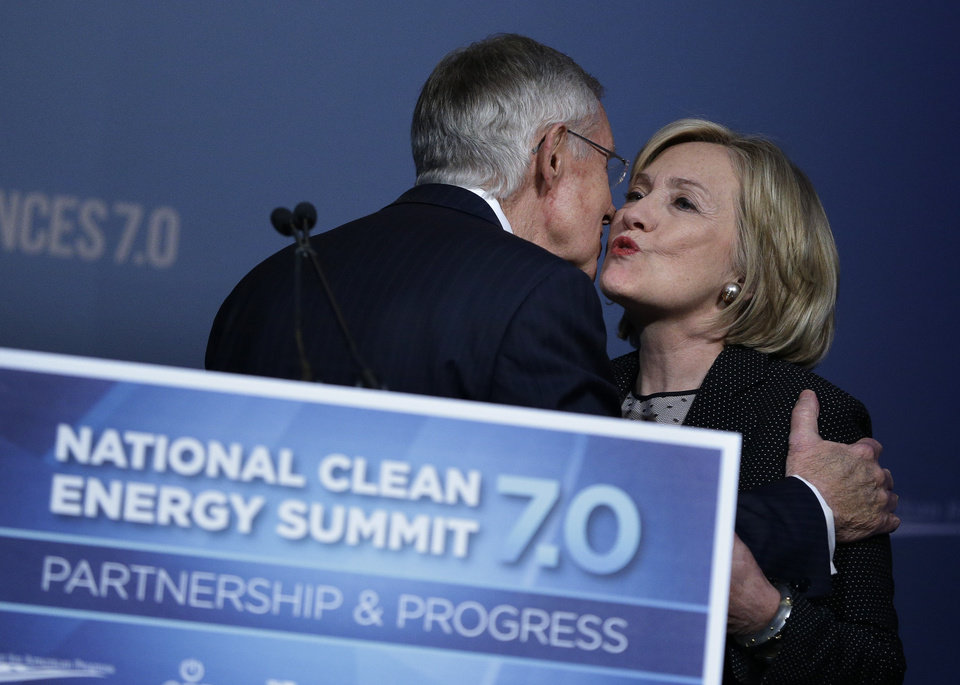 Photo - Former Secretary of State Hillary Rodham Clinton kisses Senate Majority Leader Harry Reid, D-Nev., before speaking at the National Clean Energy Summit Thursday, Sept. 4, 2014, in Las Vegas. (AP Photo/John Locher)