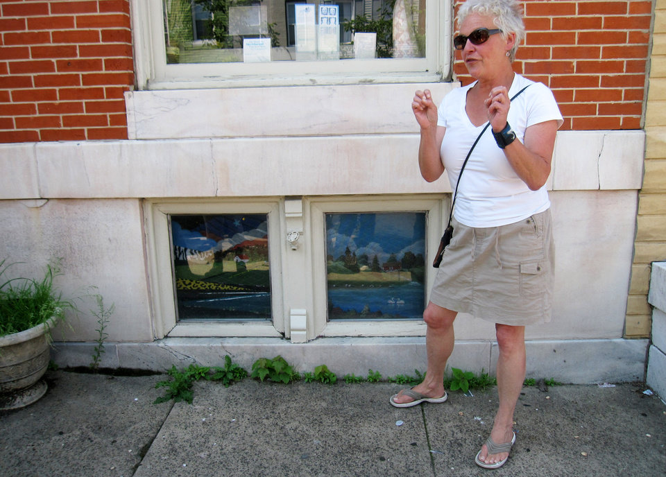 Photo - This June 8, 2014 shows artist Monica Broere talks next to painted window screens in the Highlandtown neighborhood of Baltimore. Painted screens were popular in the 20th century as a way to keep people walking by from looking inside the front windows of Baltimore's row houses. Broere and other artists are working to revitalize the urban folk tradition. (AP Photo/Beth J. Harpaz)