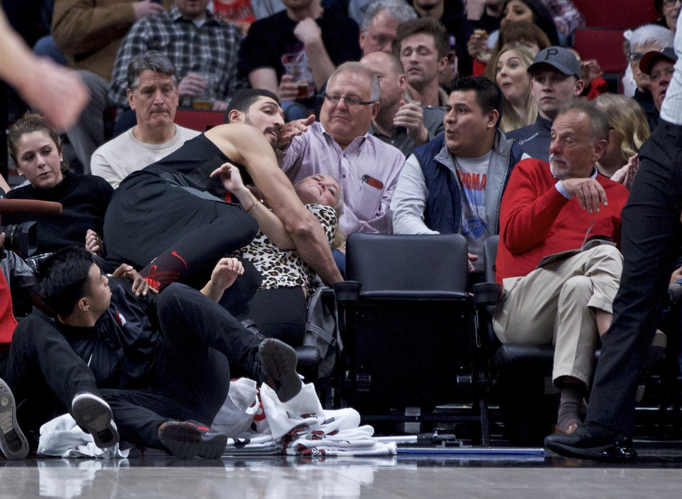 Photo - Portland Trail Blazers center Enes Kanter falls onto a spectator in the first row of seating during the first half of the team's NBA basketball game against the Oklahoma City Thunder in Portland, Ore., Thursday, March 7, 2019. (AP Photo/Craig Mitchelldyer)