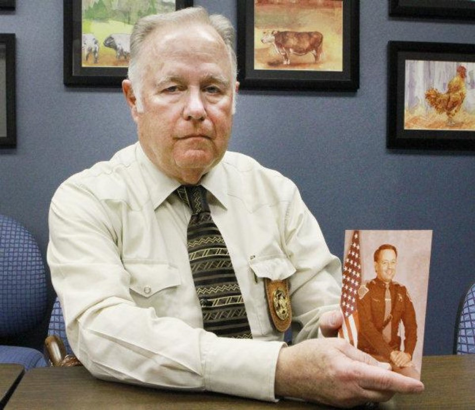 Photo - Retired Oklahoma trooper Col. Mike Grimes holds a photo of his brother, Lt. Pat Grimes, who was killed in 1978 while trying to apprehend two escaped inmates from McAlester. Photo by David McDaniel, The Oklahoman