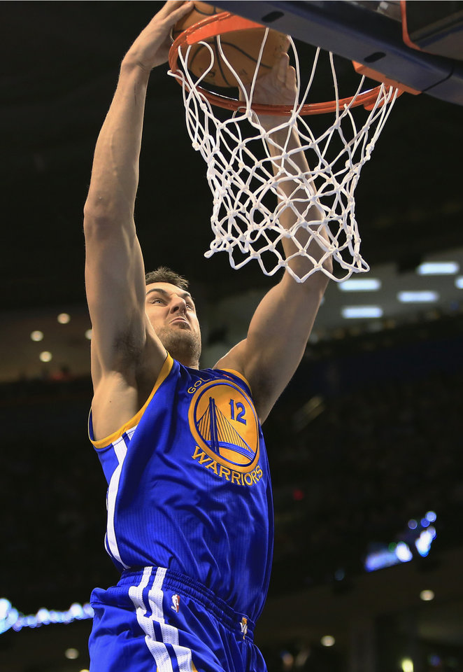 Photo - Golden State Warriors center Andrew Bogut dunks against the Oklahoma City Thunder during the first quarter of an NBA basketball game Friday, Jan. 17, 2014, in Oklahoma City. (AP Photo/Alonzo Adams)