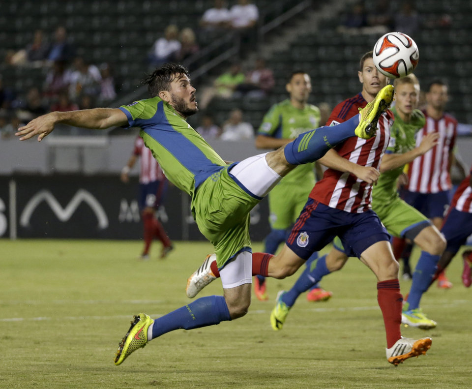 Photo - Chivas USA defender Tony Lochhead, right, watches as Seattle Sounders midfielder Brad Evans takes a shot during the first period of an MLS soccer match Wednesday, Sept. 3, 2014, in Carson, Calif. (AP Photo/Chris Carlson)