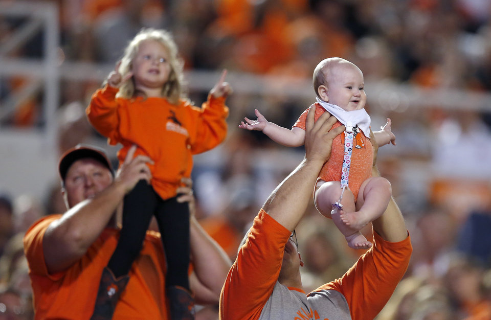 Photo - A fans holds up a baby during the Lion King Cam during a college football game between Oklahoma State (OSU) and South Alabama at Boone Pickens Stadium in Stillwater, Okla., Saturday, Sept. 8, 2018. Photo by Sarah Phipps, The Oklahoman