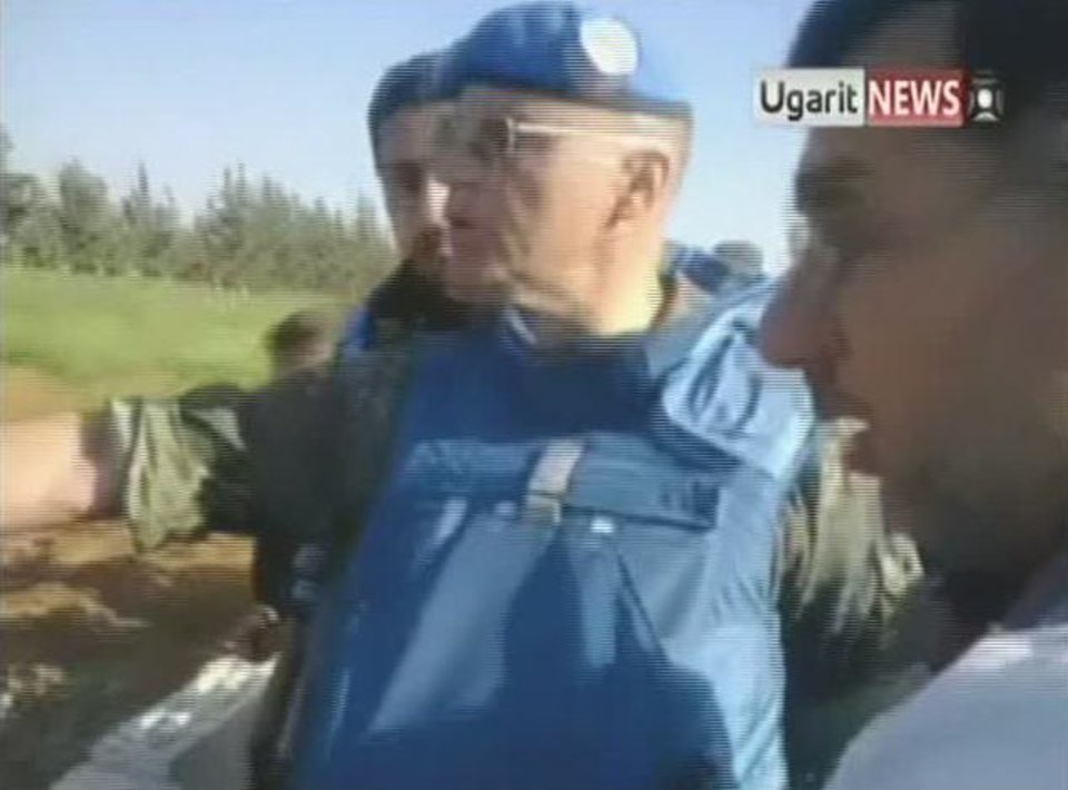 Photo -   In this image made from amateur video released by Ugarit News and accessed Saturday, May 5, 2012, a U.N. observer, center, inspects what residents of the town of Taftanaz, Syria, tell him is a mass grave. The international group Human Rights Watch has said regime soldiers raiding the town on the Turkish border in early April killed 35 detained civilians execution-style and opened fire on others trying to flee. (AP Photo/Ugarit News via AP video) TV OUT, THE ASSOCIATED PRESS CANNOT INDEPENDENTLY VERIFY THE CONTENT, DATE, LOCATION OR AUTHENTICITY OF THIS MATERIAL