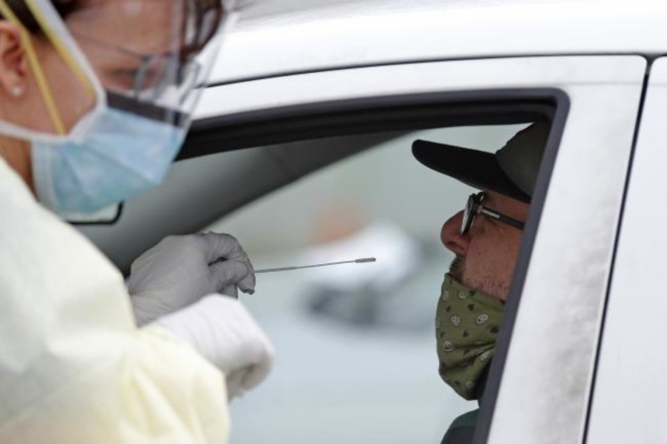 Photo -  A Cleveland County Health Department employee uses a swab to collect a sample from Christian Potts at a COVID-19 drive-thru testing site at Griffin Community Park in Norman, Okla., Thursday, April 9, 2020. [Bryan Terry/The Oklahoman]