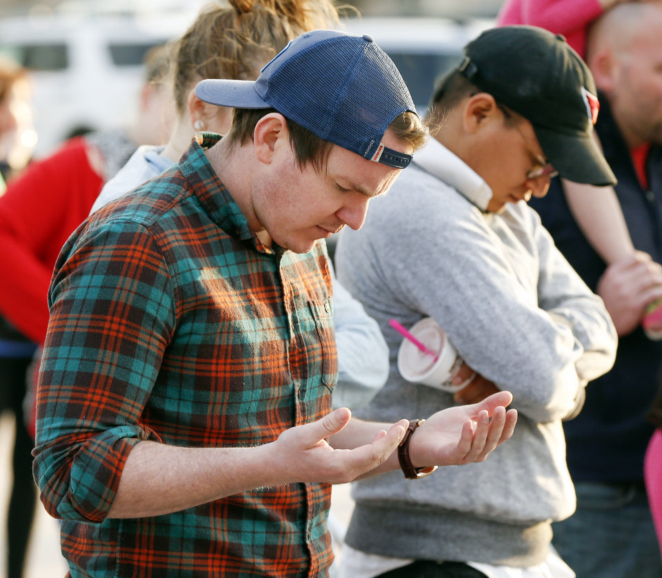 Photo -  Tyler Todd prays with others Thursday during the Churches for Teachers Prayer Vigil, an event supporting Oklahoma teachers and students, on the south side of the state Capitol in Oklahoma City. [Photo by Nate Billings, The Oklahoman]