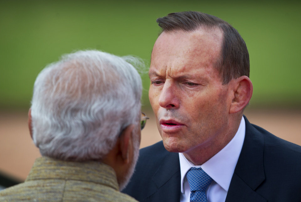 Photo - Australian Prime Minister Tony Abbott, right, speaks to his Indian counterpart Narendra Modi during his ceremonial reception in New Delhi, India, Friday, Sept. 5, 2014. Abbott is on a two-day visit to India. (AP Photo/Saurabh Das)