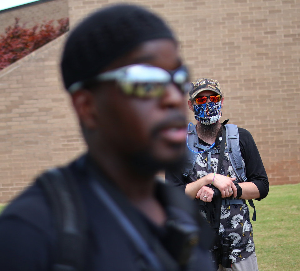 Photo - An armed man listens to Omar Chatman at a 1,000 brothers and sisters in arms for second amendment walk by predominantly black men and women to advocate for their second amendment rights, Saturday, June 20, 2020. [Doug Hoke/The Oklahoman]