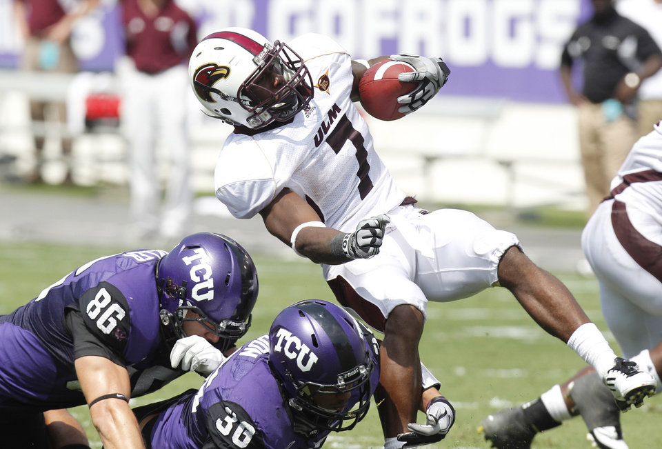 Louisiana Monroe running back Jyruss Edwards (7) is stopped by TCU tight end Corey Fuller (86) and linebacker Deryck Gildon (36) during the first half of an NCAA college football game in Fort Worth, Texas, Saturday, Sept. 17, 2011. (AP Photo/LM Otero)