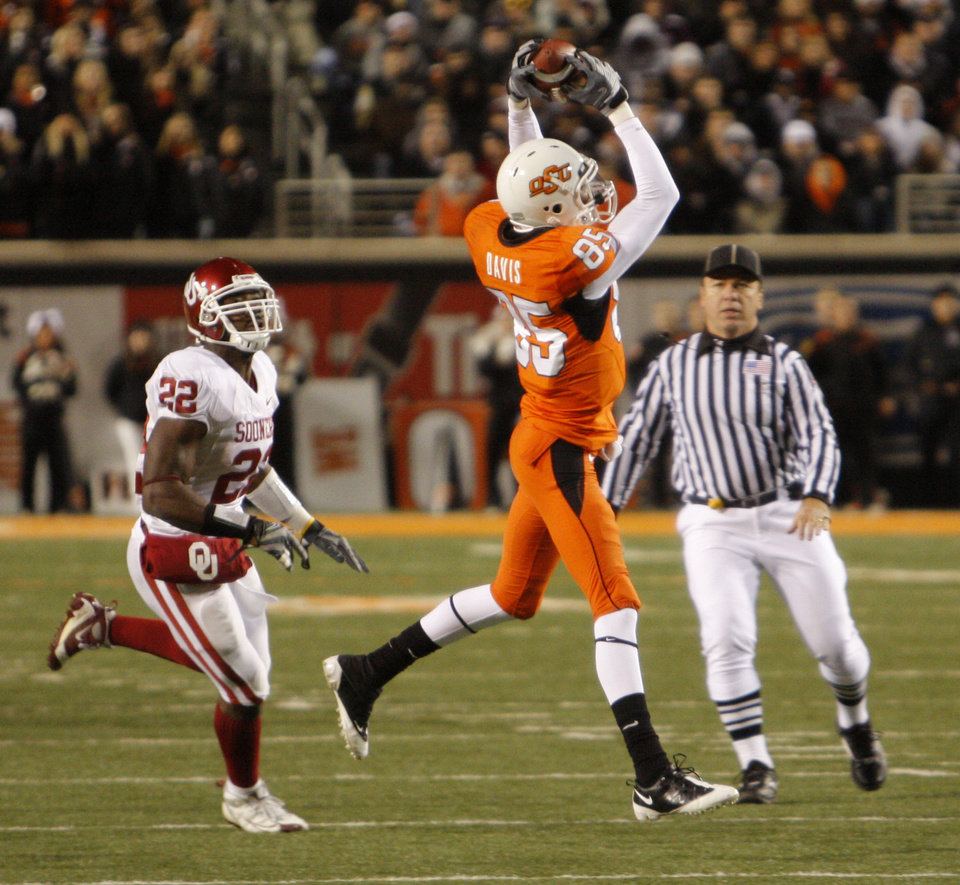 OSU's Damian Davis makes a reception in the first quarter with Keenan Clayton covering during the college football game between the University of Oklahoma Sooners (OU) and Oklahoma State University Cowboys (OSU) at Boone Pickens Stadium on Saturday, Nov. 29, 2008, in Stillwater, Okla. STAFF PHOTO BY DOUG HOKE