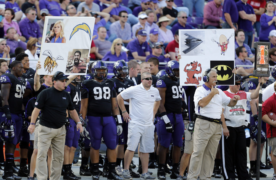 Photo - Coaches signal defenses with cards during the second half of the college football game where the University of Oklahoma Sooners (OU) defeated the Texas Christian University Horned Frogs (TCU) 24-17 at Amon G. Carter Stadium in Fort Worth, Texas, on Saturday, Dec. 1, 2012. Photo by Steve Sisney, The Oklahoman