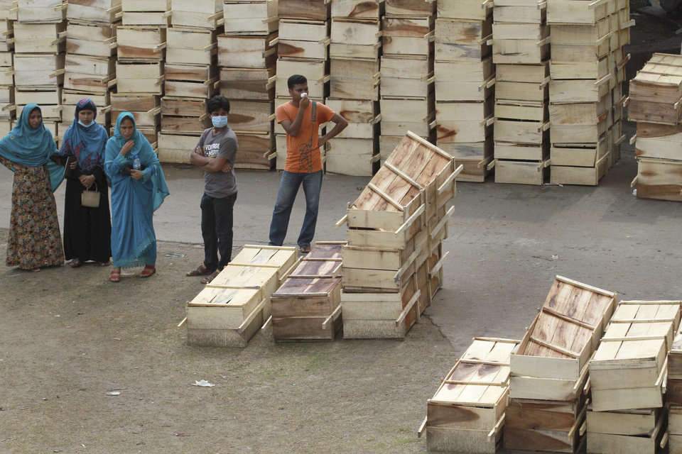 Photo - Bangladeshis stand near stacks of coffins at a makeshift morgue, meant for victims of a building the collapsed in Savar, near Dhaka, Bangladesh, Wednesday, May 8, 2013. Dozens of bodies recovered Wednesday from a collapsed garment factory building were so decomposed they were being sent to a lab for DNA identification, police said, as the death toll from Bangladesh's worst industrial disaster topped 800. (AP Photo/Ashraful Alam Tito)