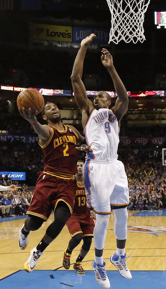 Photo - Oklahoma City's Serge Ibaka (9) tries to defend on Cleveland's Kyrie Irving (2) during the NBA basketball game between the Oklahoma City Thunder and the Cleveland Cavaliers at the Chesapeake Energy Arena in Oklahoma City, Okla. on Wednesday, Feb. 26, 2014.  Photo by Chris Landsberger, The Oklahoman