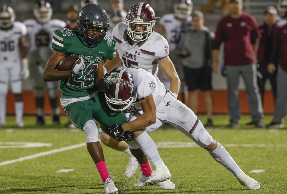 Photo - Edmond Santa Fe's Talyn Shettron, left, is tackled by Jenks during the first half of last season's game. Shettron caught the game-winning touchdown pass at Jenks this year. [Alonzo Adams for The Oklahoman]
