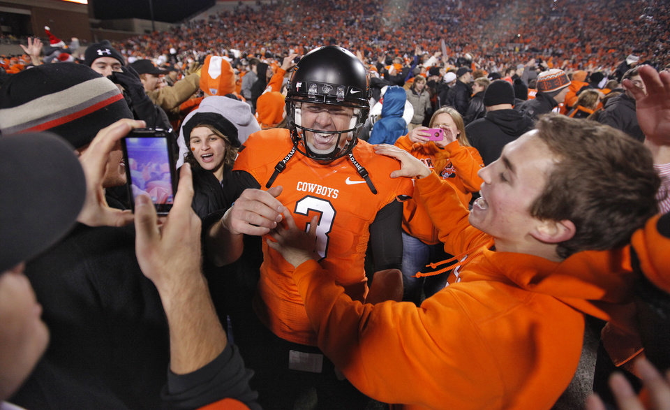 Photo - Oklahoma State's Brandon Weeden (3) celebrates with fans after the 44-10 win over Oklahoma during the Bedlam college football game between the Oklahoma State University Cowboys and the University of Oklahoma Sooners at Boone Pickens Stadium in Stillwater, Okla., Saturday, Dec. 3, 2011. Photo by Chris Landsberger, The Oklahoman