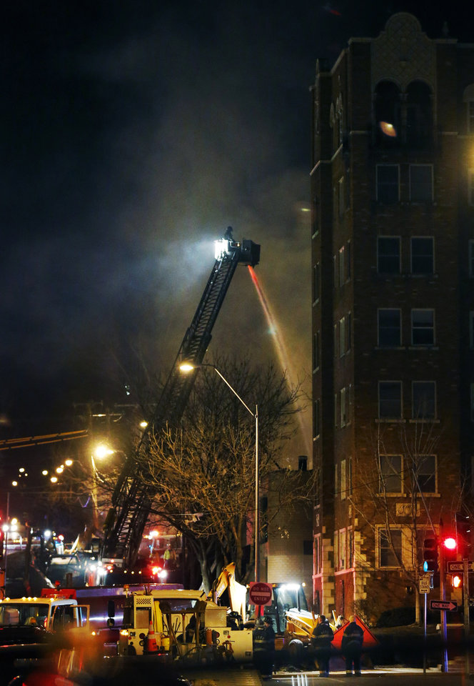 Firefighters douse a burning building at the scene of a gas explosion and massive fire Tuesday night, Feb. 19, 2013 at the Country Club Plaza in Kansas City, Mo. A car crashed into a gas main in the upscale Kansas City shopping district, sparking a massive blaze that engulfed an entire block and caused multiple injuries, police said. (AP Photo/Orlin Wagner)