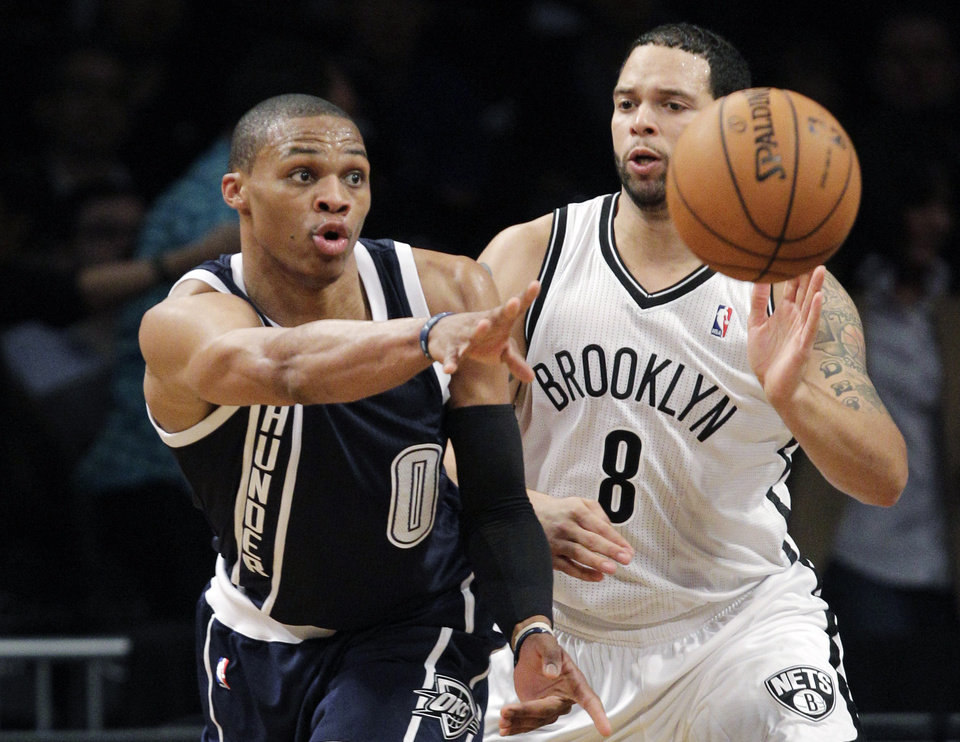 Photo - Oklahoma City Thunder guard Russell Westbrook (0) passes as Brooklyn Nets guard Deron Williams (8) defends in the first half of their NBA basketball game at Barclays Center, Tuesday, Dec. 4, 2012, in New York. (AP Photo/Kathy Willens)