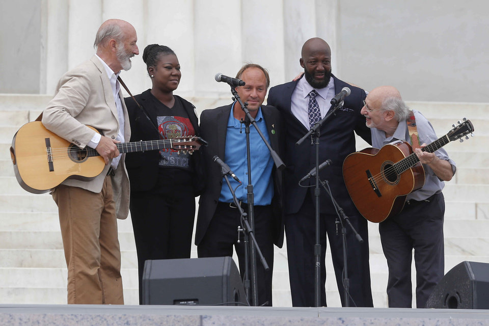 With Trayvon Martin parents, Sybrina Fulton, and Tracy Martin, and Mark Barden, father of Sandy Hook Elementary School shooting victim Daniel Barden, Peter Yarrow, left, and Paul Stookey, right, of the folk trio Peter, Paul and Mary, perform at the 50th Anniversary of the March on Washington where Martin Luther King, Jr., spoke, Wednesday, Aug. 28, 2013, in front of the Lincoln Memorial in Washington.  (AP Photo/Charles Dharapak)