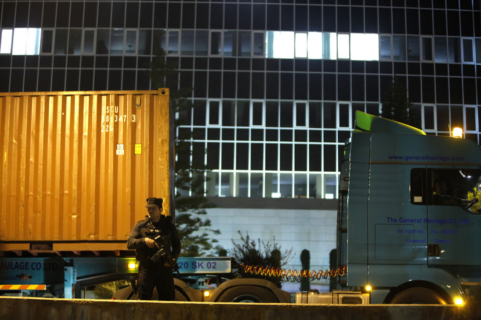 Photo - An armed police officer guards several trucks carrying containers after arriving at the country's Central Bank in Nicosia, Cyprus, on Wednesday, March 27, 2013. The contents of the trucks could not be independently confirmed, although state-run television reported they were carrying cash flown in from Frankfurt for the bank reopening.  (AP Photo/Petros Karadjias)