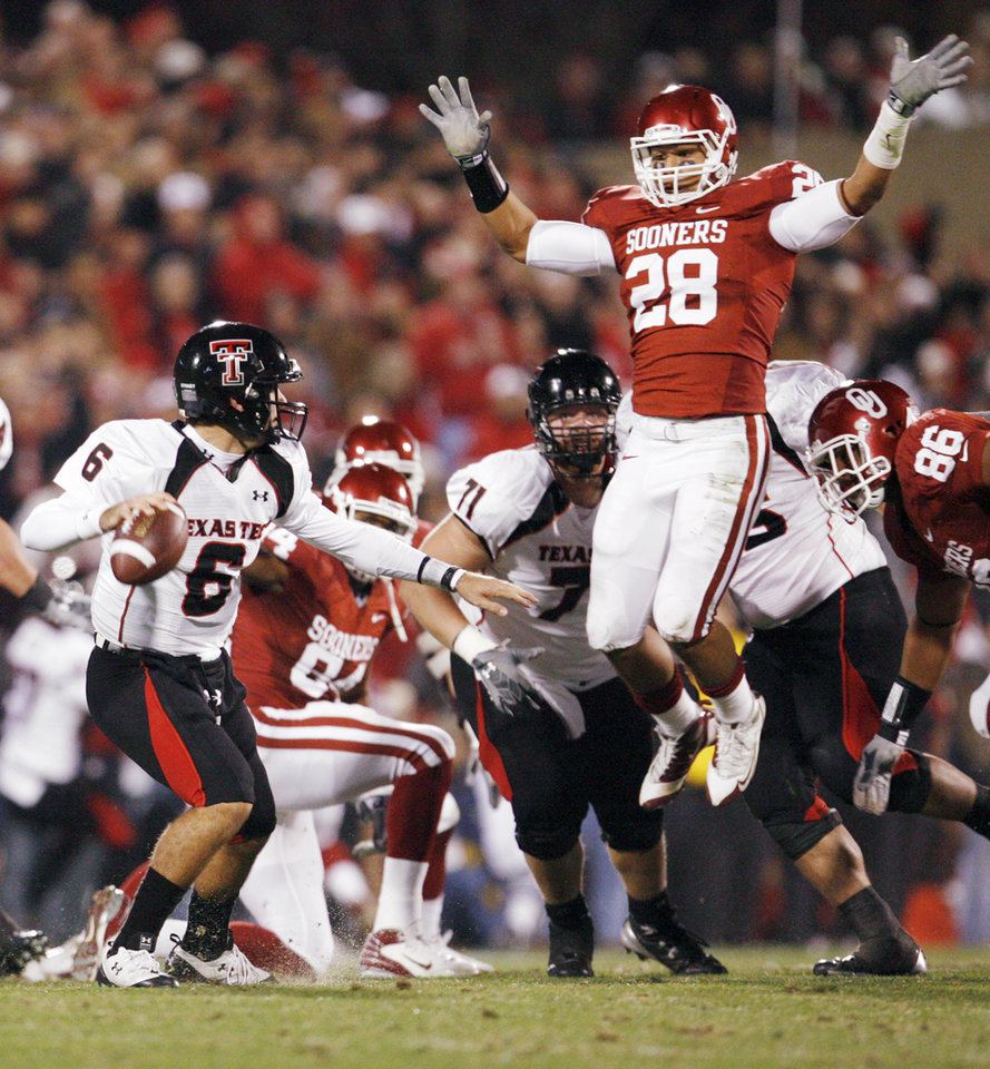 Photo - OU's Travis Lewis (28) leaps in front of Texas Tech quarterback Graham Harrell (6) in the first quarter of the college football game between the University of Oklahoma Sooners and Texas Tech University at Gaylord Family -- Oklahoma Memorial Stadium in Norman, Okla., Saturday, Nov. 22, 2008. BY NATE BILLINGS, THE OKLAHOMAN
